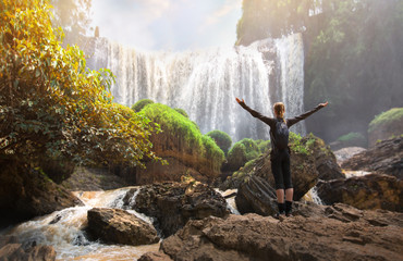 Tourist traveler standing on a rock with raised hands, hiker looking to a Elephant Waterfall below in trip in Vietnam, woman enjoying nature