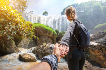 Hiker woman holding man's hand and leading him on nature outdoor below in trip in Vietnam,way to Elephant Waterfall. Couple in love. Point of view shot