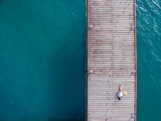 Birds eye view of woman sunbathing on wooden pier
