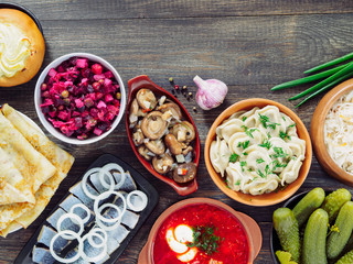 Russian food on wooden background. Assortment dishes of Russian cuisine - borscht, pelmeni, herring, marinated mushrooms, salted cucumbers, vinaigrette, sauerkraut and pancakes. Top view. Copy space.