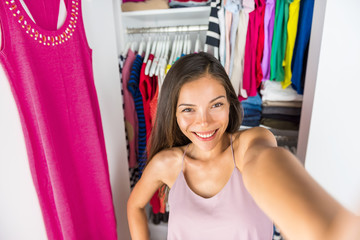 Selfie Asian girl taking photo with mobile phone of herself in closet dressing room at home trying on outfit. Clothes fashion style. Shopping girl using smartphone fashion app posting on social media.