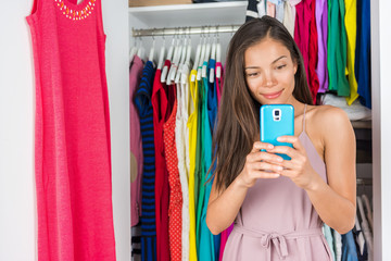 Shopping phone app fashion girl using mobile smartphone to style clothes and choose outfits in closet. Clothes wardrobe young girl taking selfie for styling.