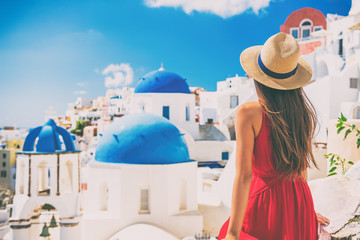 Fototapete - Tourist traveling in Santorini, Oia island in Greece, Europe travel summer vacation woman relaxing at view of three blue domes church famous attraction. holiday girl in hat and red dress enjoying sun.