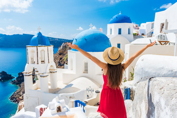 Wall Mural - Europe travel happy vacation woman. Girl tourist having fun with open arms in freedom in Santorini cruise holiday, summer european destination. Red dress and hat person.