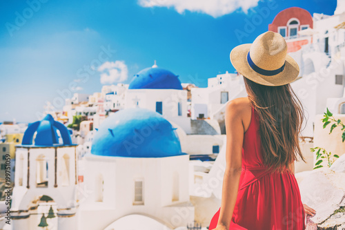 Wall mural Tourist traveling in Santorini, Oia island in Greece, Europe travel summer vacation woman relaxing at view of three blue domes church famous attraction. holiday girl in hat and red dress enjoying sun.