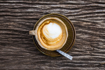 Hot latte art coffee texture on wood table