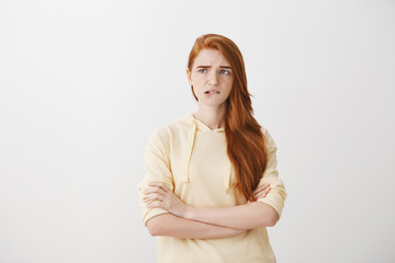 Trying to handle emotions and not to worry. Anxious redhead woman in trendy hoodie, standing with crossed hands to comfort herself, biting lip and frowning while looking aside, checking time nervously