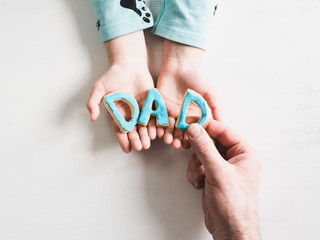 Gentle hands of a caring father and his youngest daughter, holding the letters D A D  on a white background. Close-up of the view top. Preparation for Father's Day