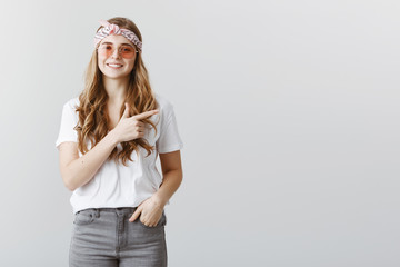 Great idea to stop by cafe. Indoor shot of beautiful creative stylish girl in headband and sunglasses pointing right with index finger while smiling broadly and friendly, showing positive attitude