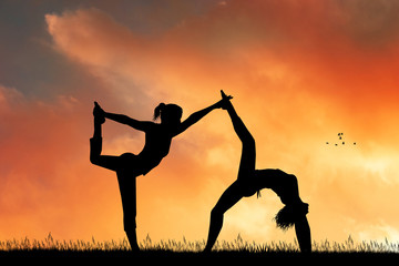 two women do yoga poses at dawn