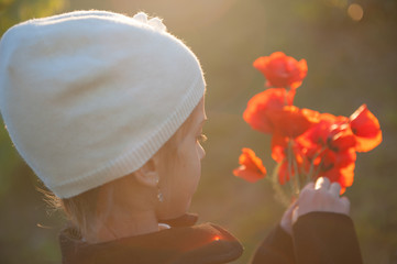 beautiful little girl with bouquet of poppies in her hands backlit by warm sunset light in May spring