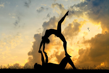 a boy and a woman do yoga at dawn