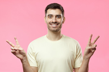 Young man isolated on pink background in beige tshirt with optimistic smile, showing victory sign with both hands, looking friendly and willing to welcome and communicate