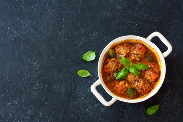Meatballs and brussel sprouts stewed in tomato sauce