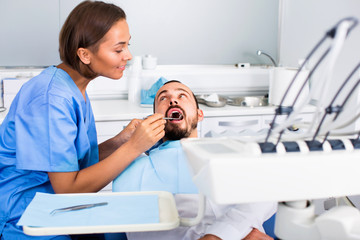 Stomatologist girl in uniform is taking visional inspection of a man