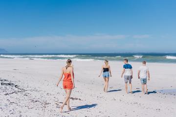 Four young friends walking across a beach
