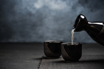 Pouring sake into sipping ceramic bowl