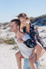 Happy loving couple piggy back riding at a beach