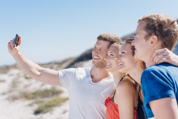 Group of young friends taking a beach selfie
