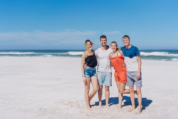 Four happy tourists posing on a beach