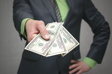 Business man holding in hands dollars money. Give money. Financial help. Bank loan. Business success concept close up background.