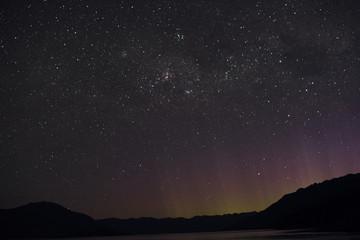 Paisaje montañoso con cielo nocturno repleto de estrellas en Nueva Zelanda.