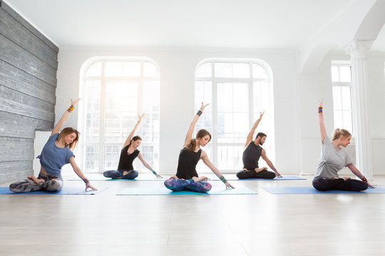 Yoga, fitness, sport and healthy lifestyle concept. Group of men and woman doing pilates exercises in gym or studio