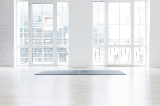 Gym white interior with black yoga mat, big windows, no people. Copy space