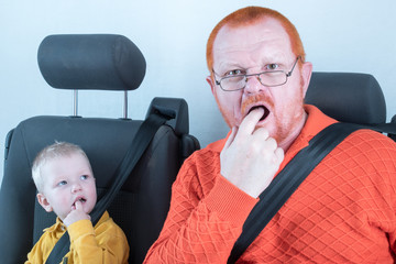 Car seat belt. A happy child is sitting in auto armchair next to man with red hair, beard and mustache in yellow shirt, glasses with laptop. The concept of road safety.