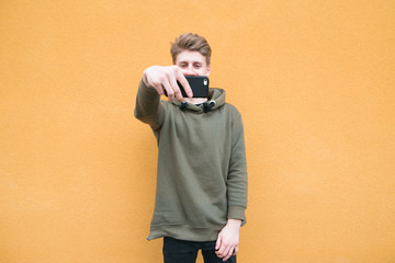 Happy student in casual clothes takes selfie on the background of an orange wall. A young man takes a photo on a smartphone