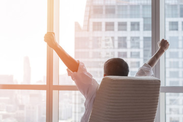Business achievement concept with happy  businessman relaxing at work in office room, resting and raising fists with ambition success looking forward to future vision at city building urban scene