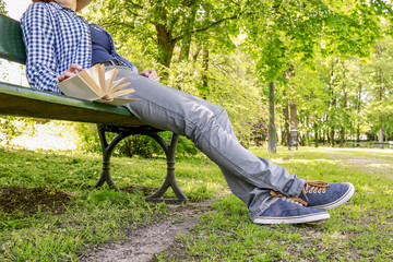 Woman reading a book, sitting on the bench in a park
