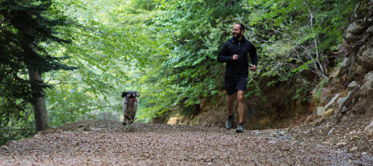 man running with his dog around the forest