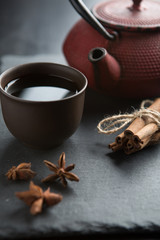 Red iron teapot and traditional ceramic cup of tea over dark texture background.