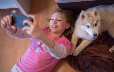 Happy young kid taking a selfie with her husky dog puppy