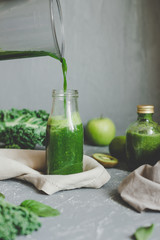 Hands pouring healthy green smoothie in a jar. Clean eating concept