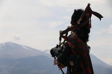 Fototapeta mężczyzna w tradycyjnym szkockim stroju grający na kobzie oraz najwyższy szczyt szkocji w tle