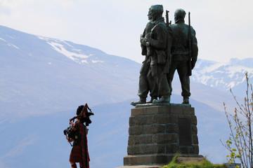 Fototapeta pomnik w szkocji upamiętniający żołnierzy poległych w walce oraz grający na kobzie szkot i góry w tle