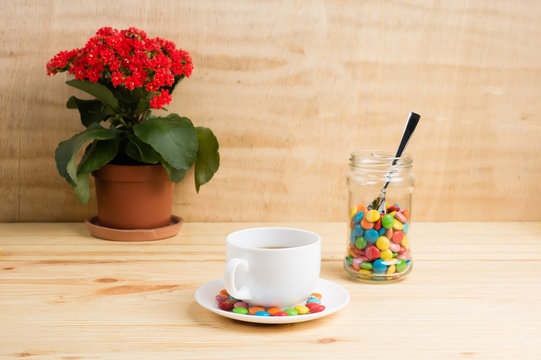 Coffee mug, red flowers, colored candy in a jar and a yellow diary on a wooden background. breakfast or lunch