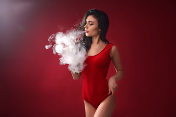 Young sexy woman in red body is vaping. A cloud of vapor. Studio shooting.
