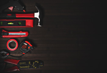 tools for home repair in red style on a black wooden background