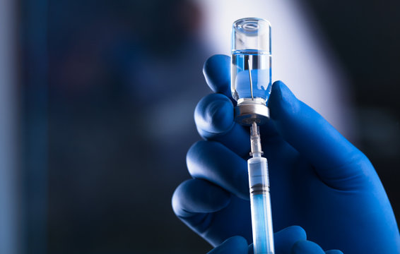 Medical hands holds syringe and vaccine
