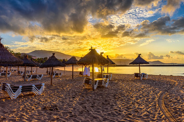 Sunrise view of beach Playa Del Caminson with sun loungers and umbrellas at sunrise, Playa de la Americas on Tenerife, Canary Islands in Spain