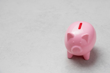 Piggy bank pink color filled with coins on concrete background.Saving investment concept.