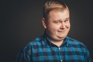 Portrait of smiling fat man on black background