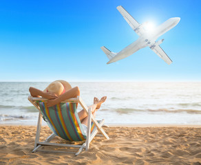 Woman on beach and airplane in summer