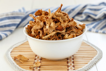 Dry chanterelles mushrooms in a white plate on a white wooden background