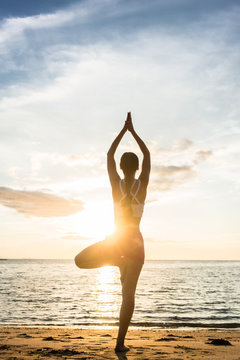Full length rear view of the silhouette of a woman standing on one leg, while practicing the tree yoga pose on a tranquil beach at sunset during summer vacation in Indonesia