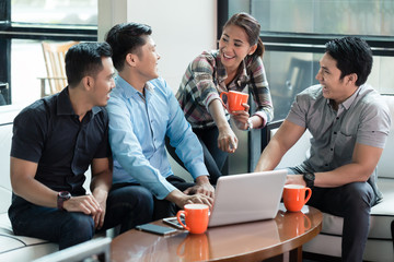 Two cheerful Chinese young men using a laptop while sharing business ideas with their colleagues during work in a successful multinational company