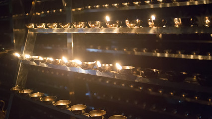 Candle flame close-up. Many Candles in a Buddhist temple. Religious Festival. Oil Lamp